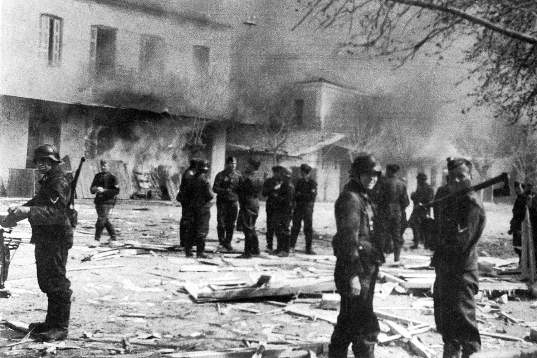 Deutsche Soldaten am 10. Juni 1944 vor brennenden Häusern in Distomoam