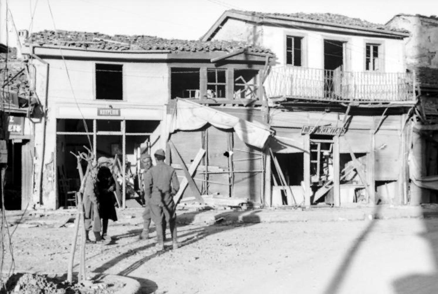 Deutsche Wehrmachtsangehörige und griechische Zivilist*innen vor zerstörten Häusern